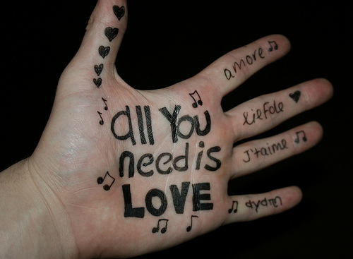 Una mano con All You Need is Love escrito